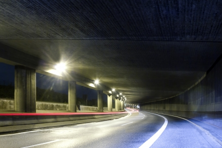 Modern street tunel with one open side and light trails of a moving car Stock Photo