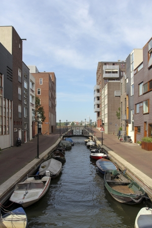 Modern residential area in Amsterdam with small canal and boats photo