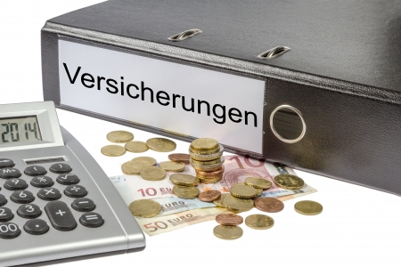 A Binder labeled wit the word Versicherungen  German insurance , calculator and european currency
