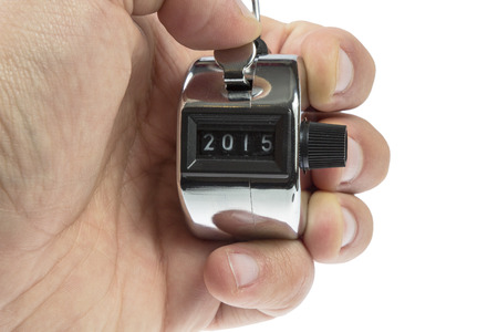Hand held tally counter showing 2015 holded by male hand isolated on white background photo