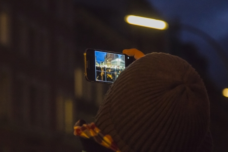 reeperbahn: HAMBURG, GERMANY - JANUARY 11: A man takes a picture of the demonstration against the police tactics of the last weeks on January 11, 2013 in Hamburg. Editorial
