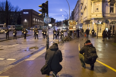 reeperbahn: HAMBURG, GERMANY - JANUARY 11: Two photographers takeing pictures of the riot police escorting a demonstration on January 11, 2013 in Hamburg