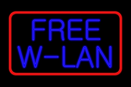 Illuminated Neon sign with blue Letters and red frame showing free w-lan isolated on black background photo