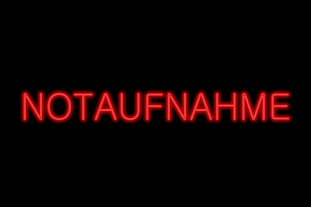 Illuminated Neon sign showing notaufnahme (german emergency room) in red letters isolated on black background photo