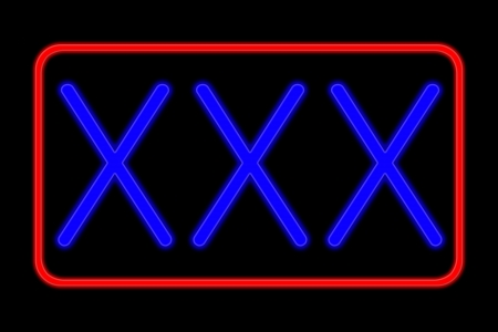 Illuminated Neon sign with blue Letters and red frame showing xxx isolated on black background