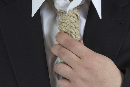 Businessman wearing a hangman's noose instead of a tie around the neck photo