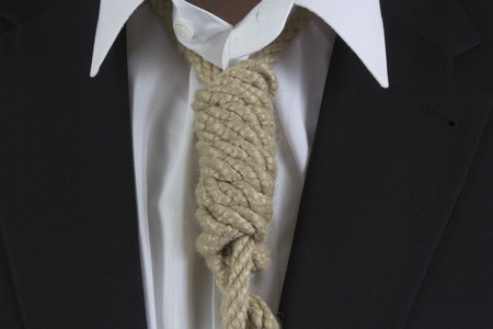 Businessman wearing a hangmans noose instead of a tie around the neck Stock Photo