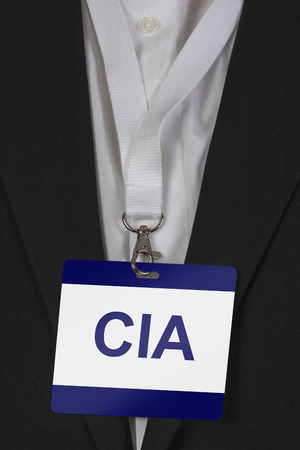man in suite wearing pass labeled CIA arround his neck