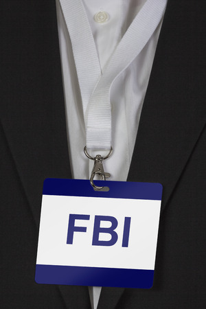 man in suite wearing pass labeled FBI arround his neck