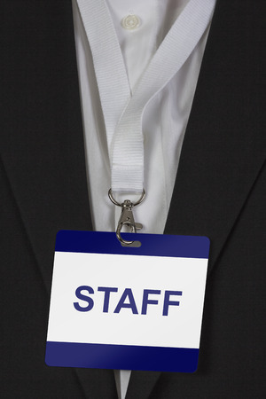 neckband: man in suite wearing a Staff pass arround his neck