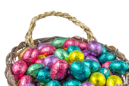chocolate easter eggs wrapped in colorful aluminum foil in a basket isolated on white background photo