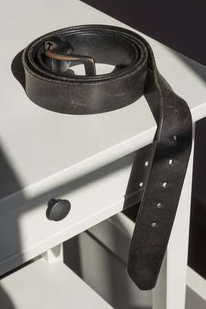 Rolled up black leather mens belt on a white bedstand