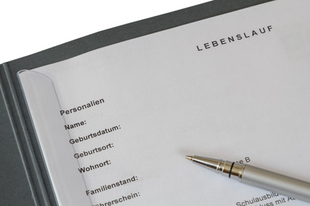 Lebenslauf (german curriculum vitae) in a job application binder and a silver pen isolated on white background photo