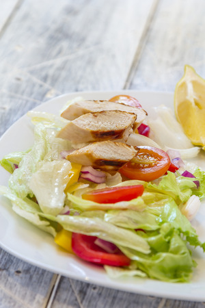 Green Salad with chicken breast filet, Tomatoes red and yellow pepper and red onions on a plate