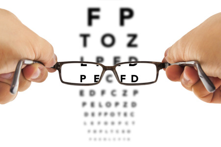 eye exam: glasses beeing hold in front of an alphabet eyesight test charts isolated on white background