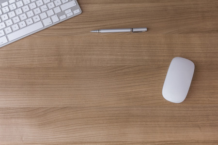 A wooden Desk with a modern keyboard, mouse and a pen with\ copy space in the middle