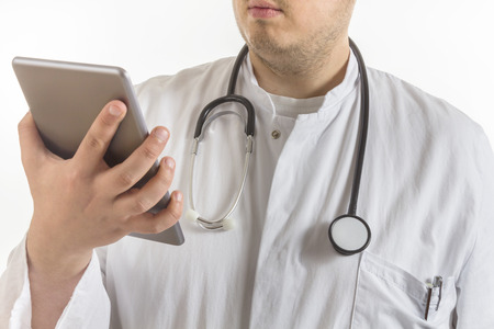 Young Doctor with laboratory coat and stethoscope looking at a tablet computer isolated on white background