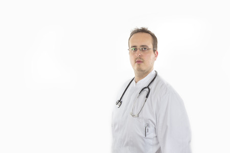sidewards: Young Doctor with laboratory coat and stethoscope standing sidewards to the camera isolated on white background