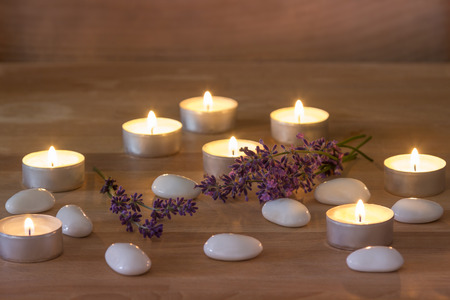 Tea Candles with white stones and lavender on rustic wooden background photo