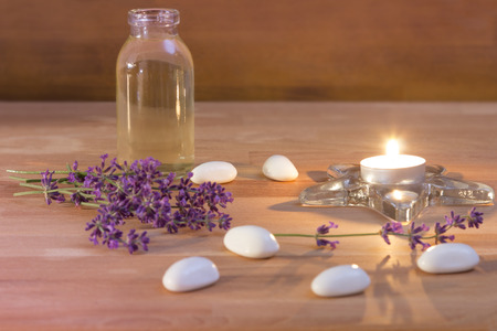 A Tea candle with a bottle of oil white stones and lavender on rustic wooden background photo