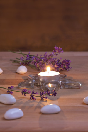 A Tea Candle with white stones and lavender on rustic wooden background photo