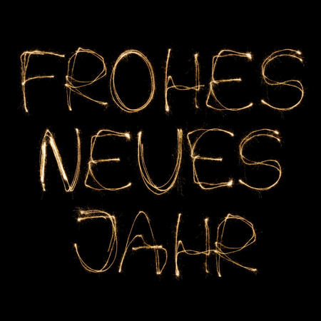 sparkler: Frohes neues Jahr (German Happy new Year) written with a sparkler isolated on black background