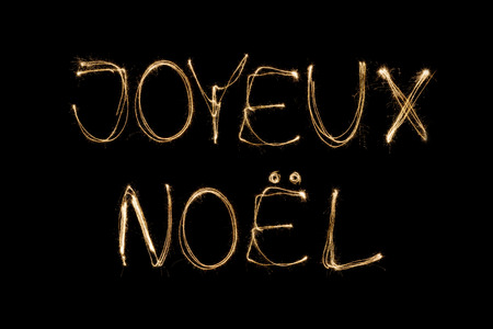 joyeux: Joyeux Noel (French Merry Christmas) written with a sparkler isolated on black background