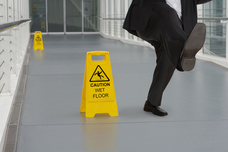 Man in suit slipping on wet floor with several warning signs