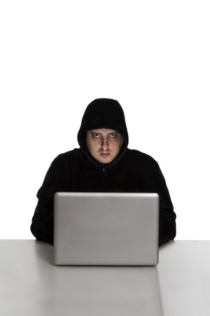 Hacker in black dress on a silver laptop computer isolated on white background