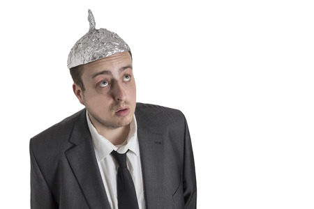 conspiracy: distraught looking conspiracy believer in suit with aluminum foil head isolated on white background Stock Photo