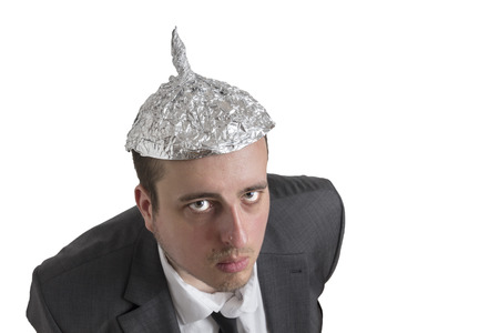 new world order: distraught looking conspiracy believer in suit with aluminum foil head isolated on white background Stock Photo