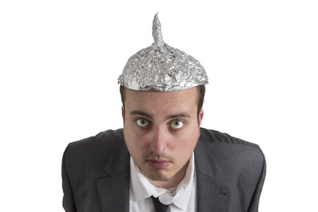distraught: distraught looking conspiracy believer in suit with aluminum foil head isolated on white background Stock Photo