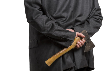 mistrust: Man in suit hiding an axe behind his back isolated on white background