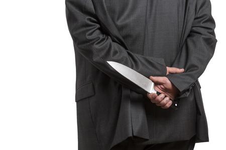 desconfianza: Hombre en el juego que oculta un gran cuchillo a la espalda aislado en fondo blanco Foto de archivo