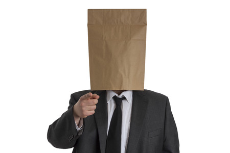 embarrassing: A Man in suit with a paper bag on his head pointing into the camera isolated on white background Stock Photo