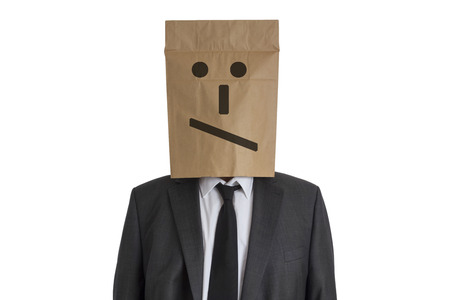 embarrassing: A Man in suit with a paper bag with disappointed smiley on his head isolated on white background