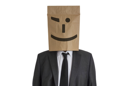 embarrassing: A Man in suit with a paper bag with twinkle smiley on his head isolated on white background Stock Photo