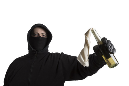 molotov: Hooded man in black dress holding a molotov cocktail isolated on white background Stock Photo