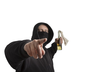 Hooded man in black dress holding a molotov cocktail pointing into the camera isolated on white background photo