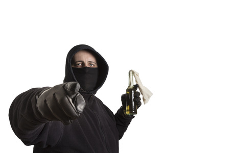 molotov: Hooded man in black dress holding a molotov cocktail pointing into the camera isolated on white background
