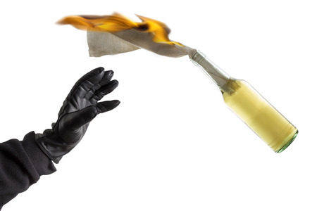 molotov: Arm in black sleeve with black leather glove thwowing a Molotov Cocktail with burning fuse, isolated on white background Stock Photo