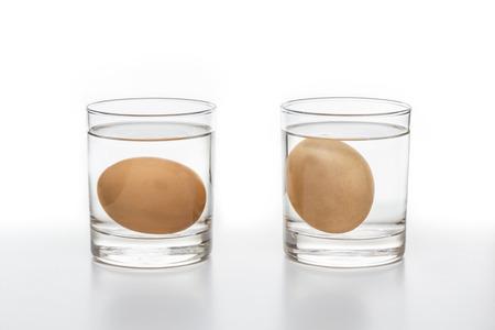 huevo blanco: Dos vasos de agua con un huevo fresco de la izquierda y un huevo podrido en el lado derecho aislado en fondo blanco