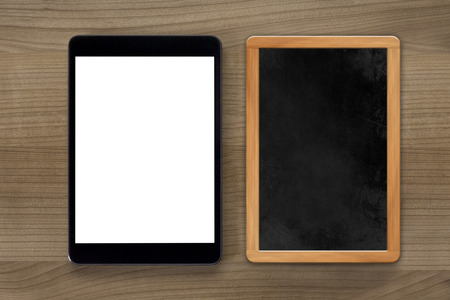 allusion: A tablet computer and a vintage chalkboard on a wooden desktop