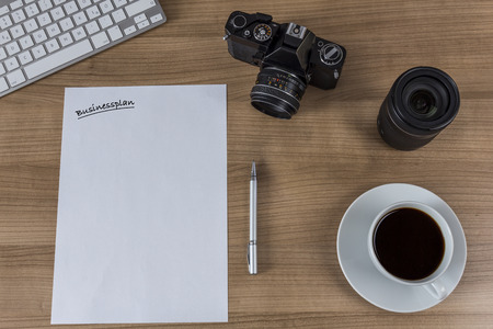businessplan: A sheet with the word businessplan, a modern keyboard, vintage camera and a cup of coffee on a wooden desktop