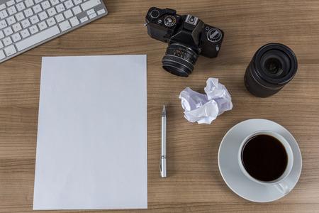 hoja en blanco: Una hoja en blanco, moderno teclado, c�mara de la vendimia y una taza de caf� en una mesa de madera Foto de archivo