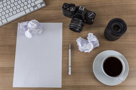 hoja en blanco: Una hoja en blanco con el papel desmenuzado, moderno teclado, c�mara de la vendimia y una taza de caf� en una mesa de madera Foto de archivo