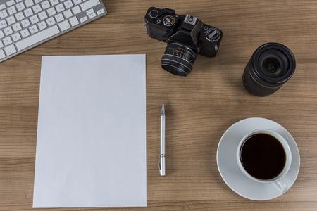 blank sheet: Una hoja en blanco, moderno teclado, c�mara de la vendimia y una taza de caf� en una mesa de madera Foto de archivo