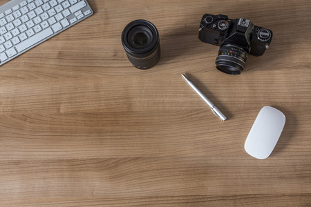 e work: Modern keyboard and a vintage camera on a wooden desktop