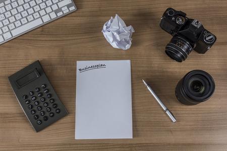 Clavier moderne, calculatrice, feuille avec le mot business plan, appareil photo vintage et un stylo sur un bureau en bois