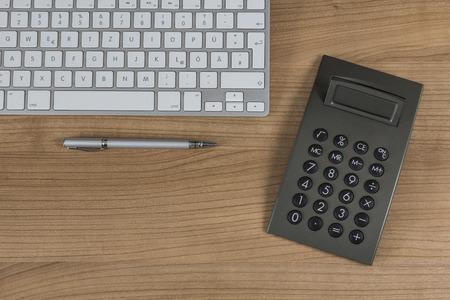 Modern keyboard, pen and a calculator on wooden Desktop